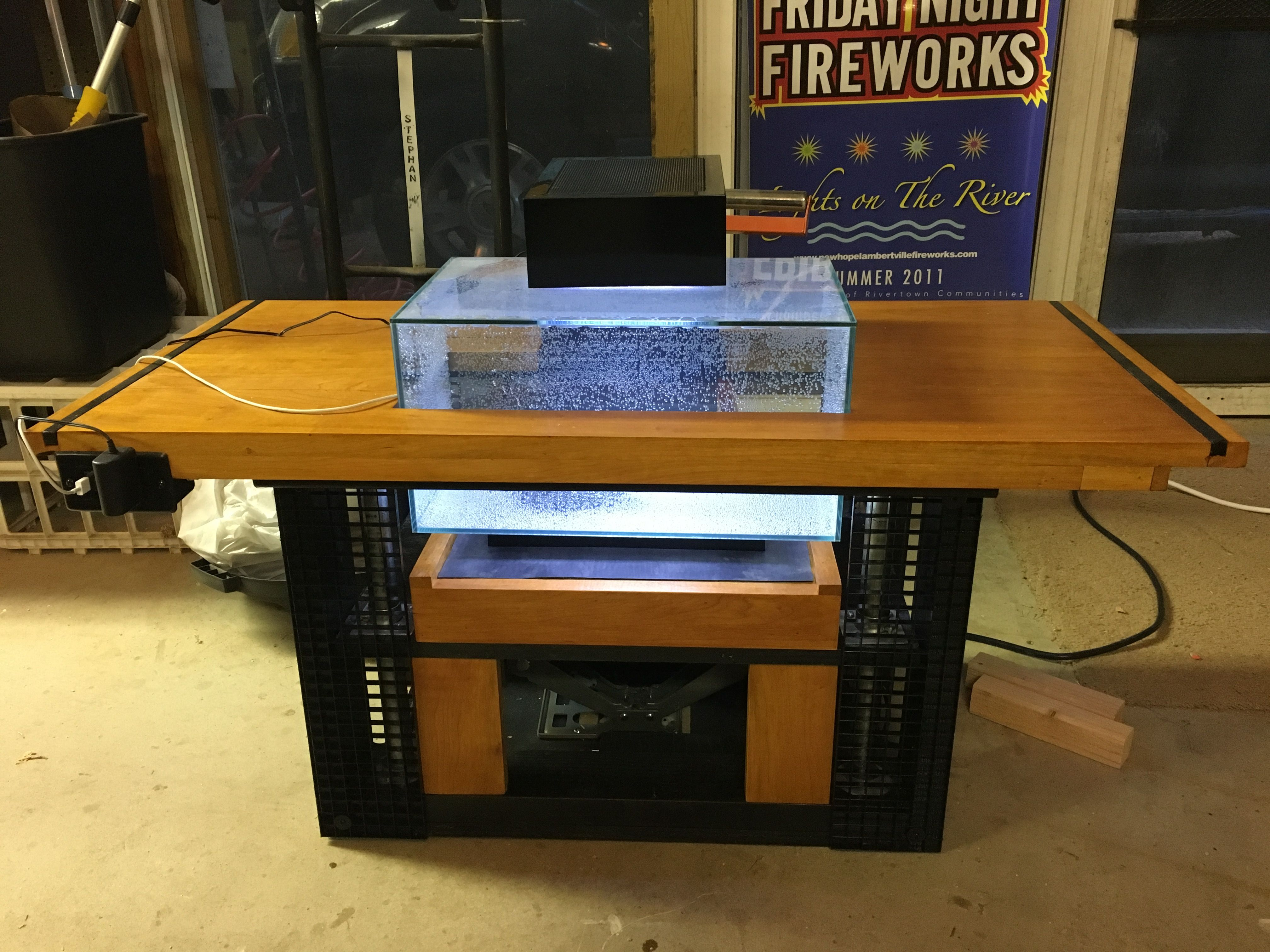 Fish tank coffee table An automatic car jack lifts the tank up and