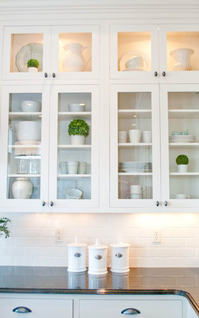White upper cabinets to the ceiling  with lit top glass doors No on long uppers Love little pops of green in clean white dishes For