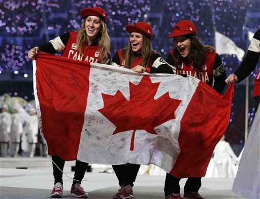 Canadian athletes hold up the national flag as they arrive during the closing ceremony of the 2014 Winter Olympics, Sunday, Feb. 23, 2014, in Sochi, Russia.  (AP Photo/Darron Cummings)