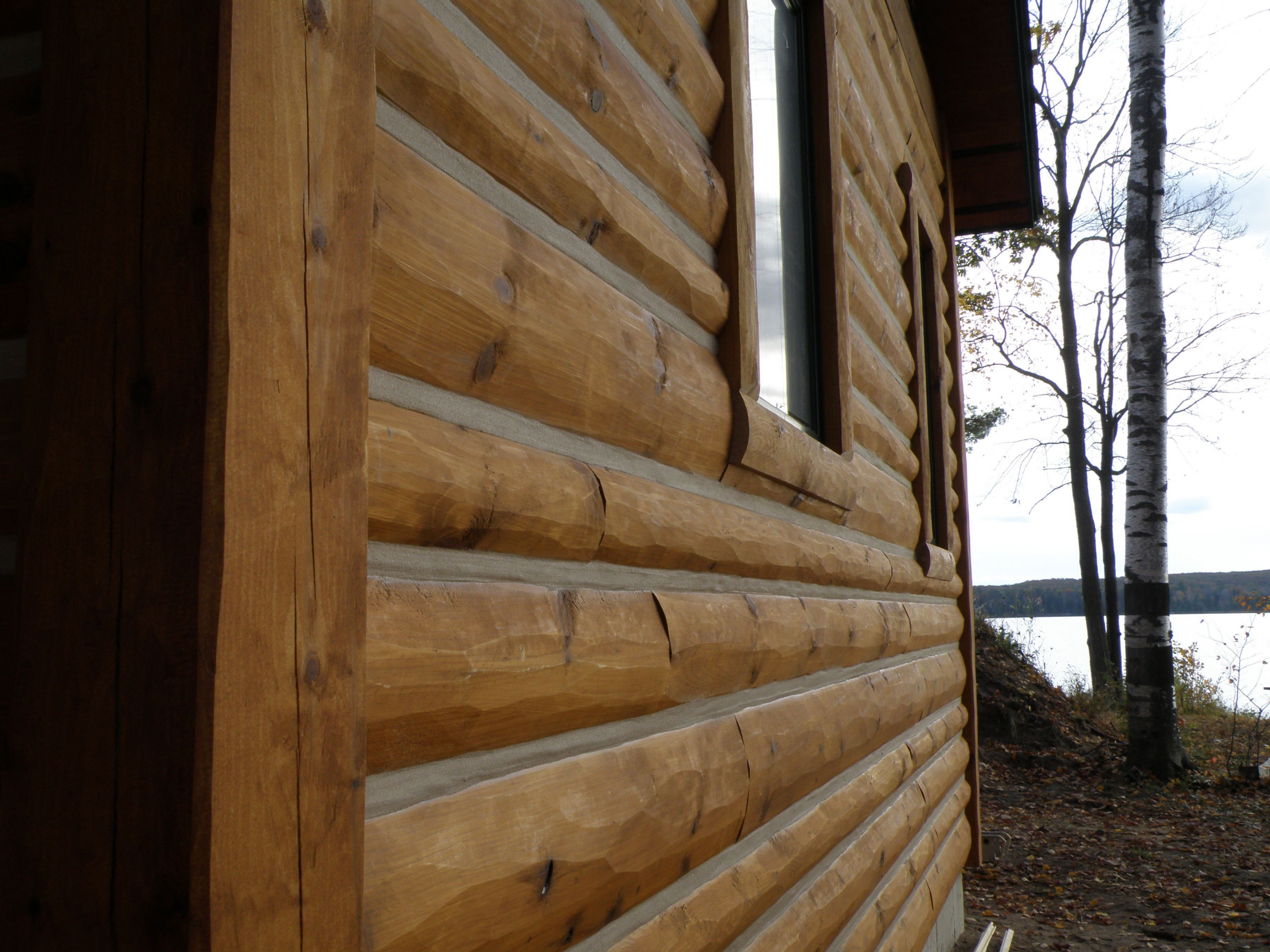 Mixed width half log siding with chinking strip home for Chinking log cabin