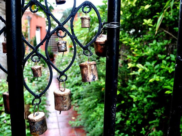 Un petit portail en fer forgé agrémenté de clochettes dans un jardin