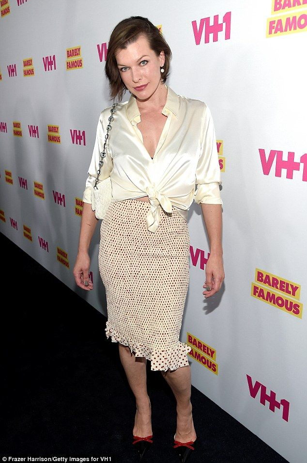 Kiev-born beauty: The 40-year-old actress paired her white top with a matching quilted purse, red-dotted pencil skirt, and red-bowed patent leather pumps