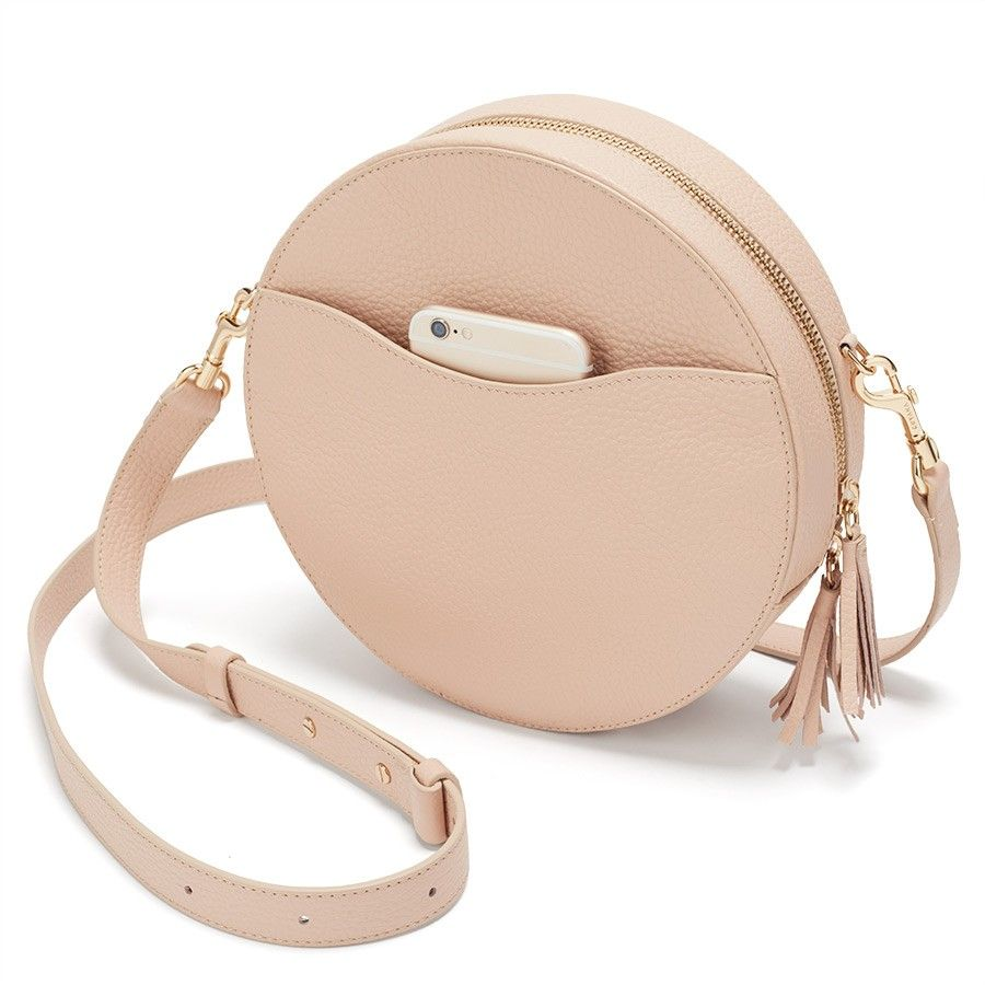 The Cuyana Circle Crossbody Bag was designed as a playful addition to your handbag collection. Expect our signature C-curve exterior pocket for seamless access to your mobile phone and other essentials. Women's Circle Crossbody Bag In Blush Pink | Pebbled Leather