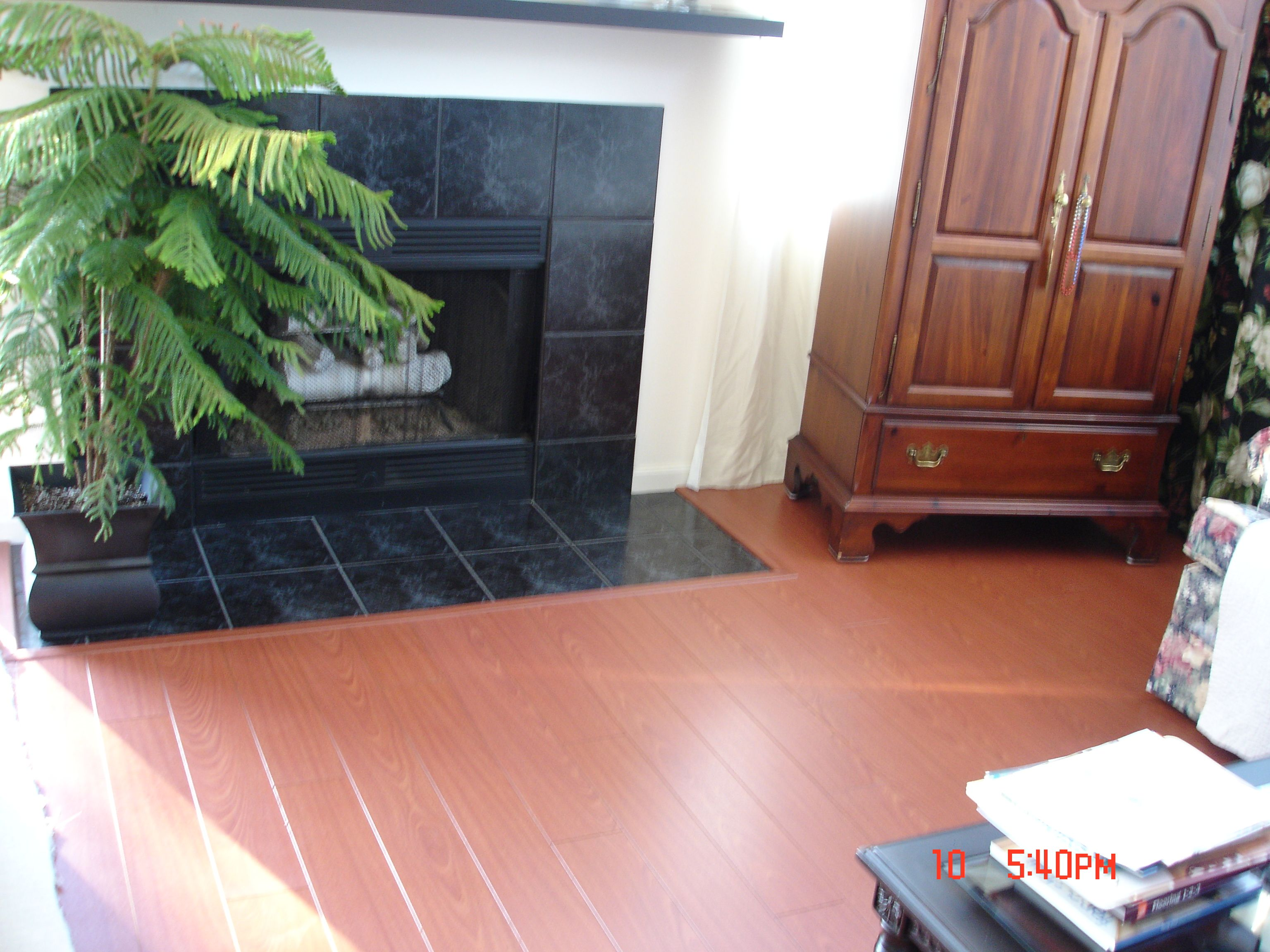 Finished laminate flooring around fireplace tile with trim