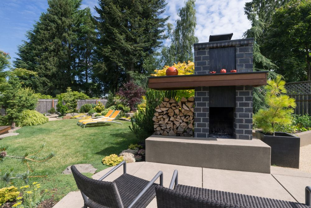 This simple concrete backyard patio has a wood-burning fireplace.
