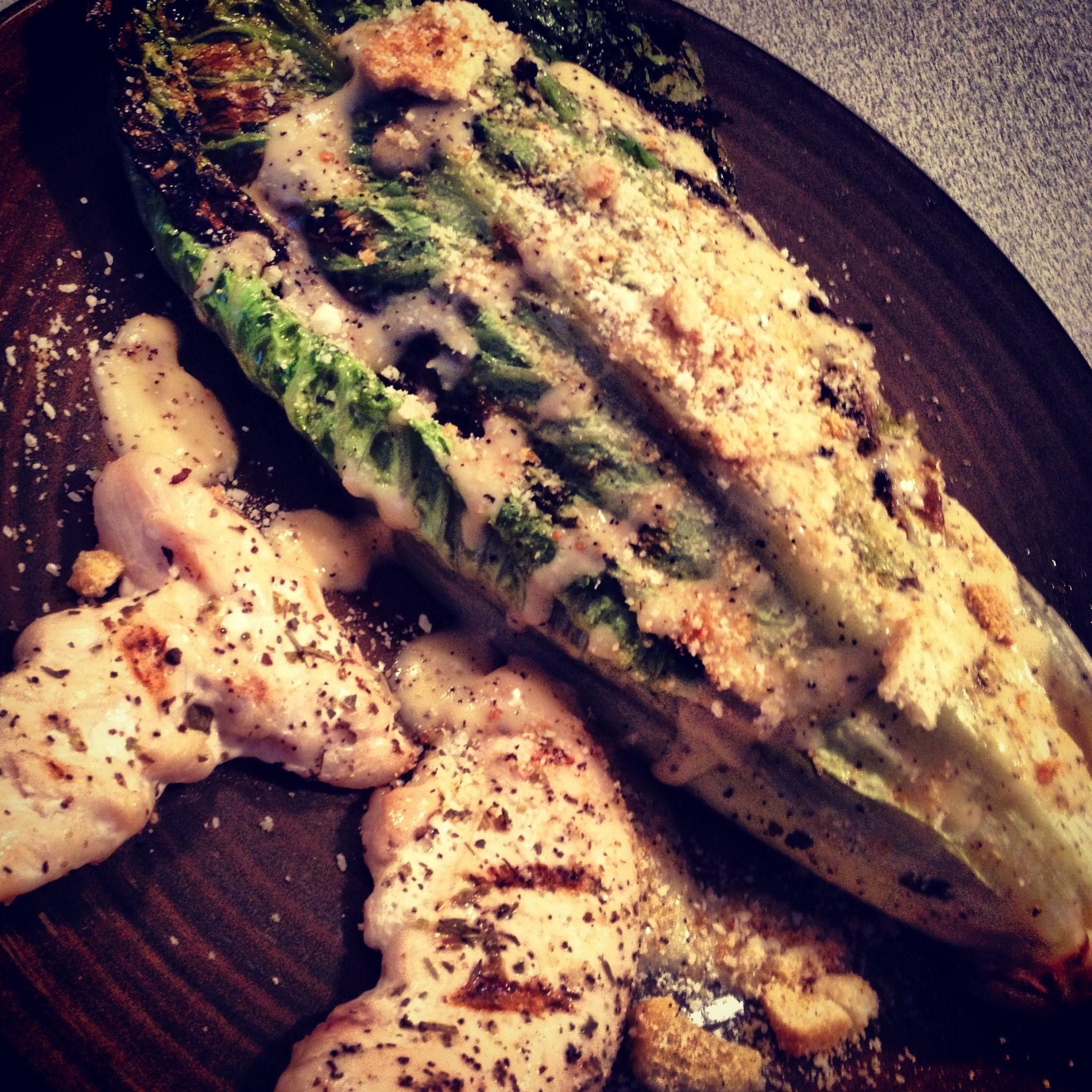 Grilled romaine Caesar salad with grilled chicken.