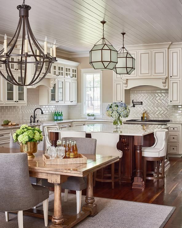 Traditional kitchen features ivory cabinets adorned with bronze hardware paired with white marble countertops and a cream subway tiled backsplash.