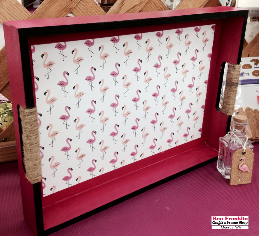 """This Flamingo Wood Tray was painted in dark pink first, then we added black paint to the edges. We glued the flamingo paper (which is part of the Imaginisce """"Sunny"""" paper collection) to the bottom of the tray. We used Mod Podge to glue the paper, and applied a top coat to seal and protect the paper. The last thing was to wrap jute around the handles. Use a good strong glue to hold in place. We used E6000. 