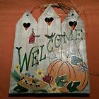 Wood fence welcome sign for fall with pumpkins corn and fall leaves