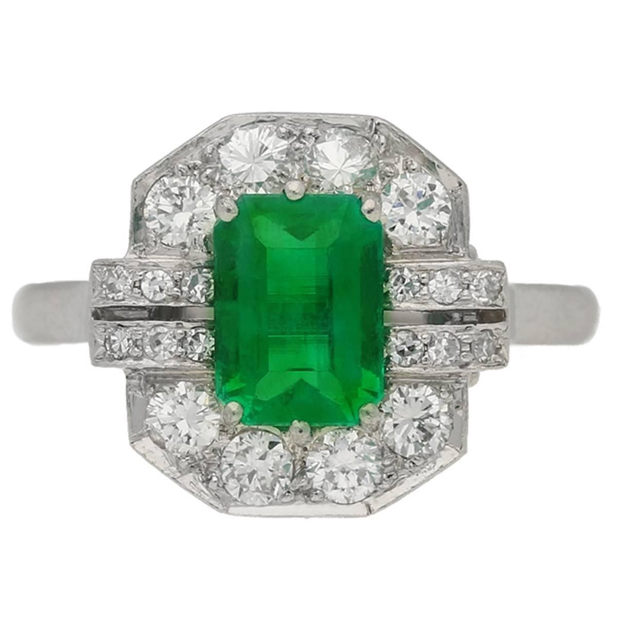 Art Deco emerald diamond Platinum Engagement ring. Set with an octagonal emerald-cut natural Colombian emerald with no colour enhancement in an open back claw setting with an approximate weight of 1.38 carats, encircled by eight round old cut diamonds in open back grain settings and flanked by two rows of round single cut diamonds, 1935