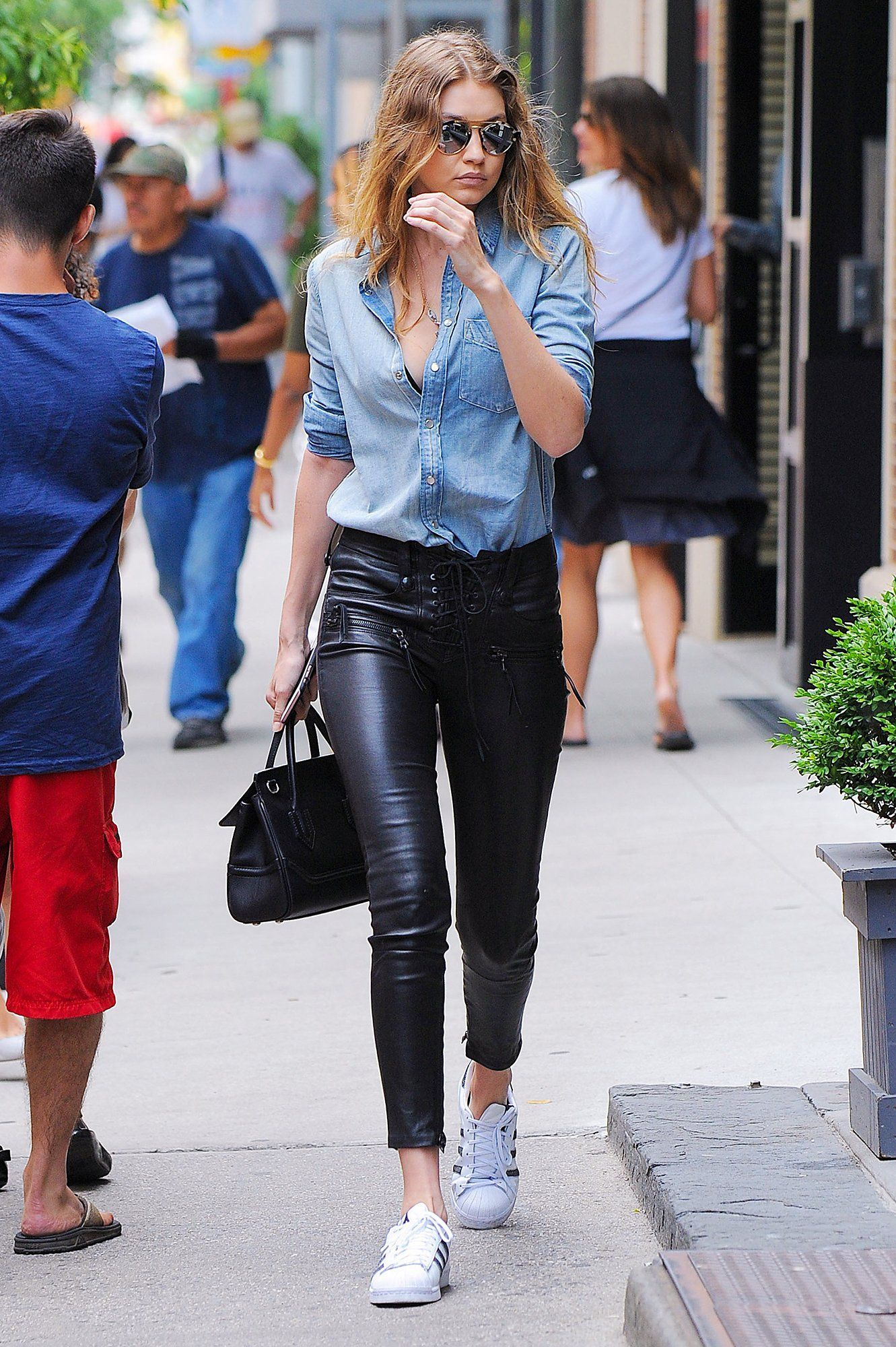 aa6a13d2b406d9 Gigi Hadid in lace-up leather trousers, chambray shirt, Adidas sneakers and  a Versace tote.