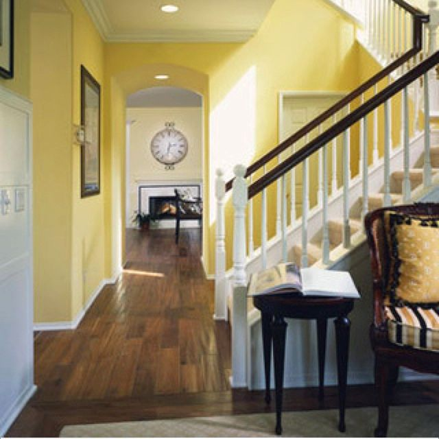 Yellow in the living room beyond creates continuity between the ...
