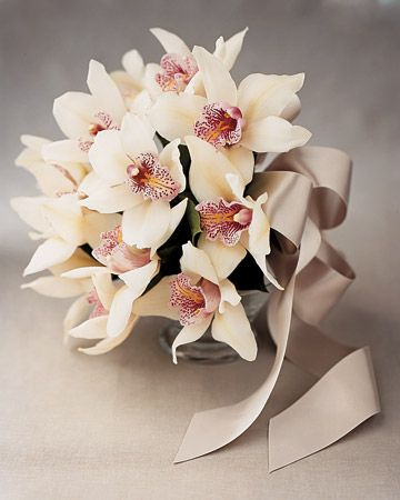 This elegant bouquet of cheerful white cymbidium orchids is tied with a silver-gray ribbon.