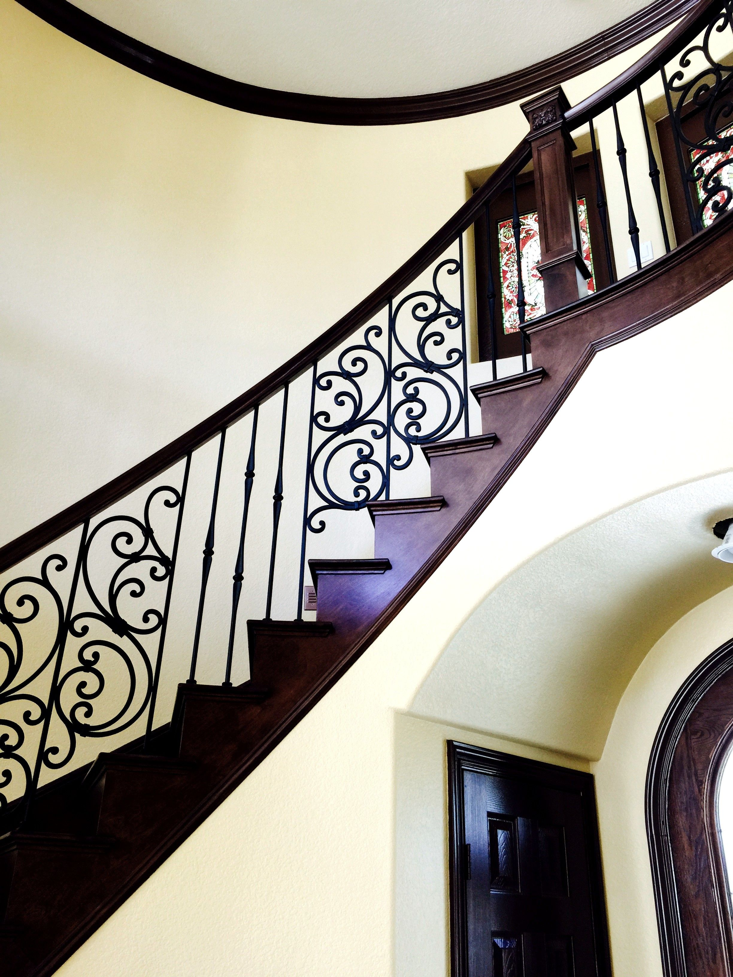 dark wood trim wrought iron rails dramatic staircase by maverick