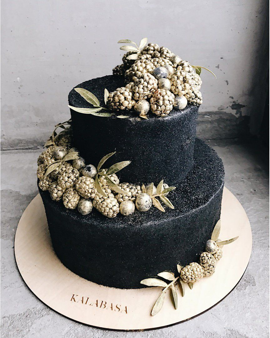 Black wedding cake topped with gold berries
