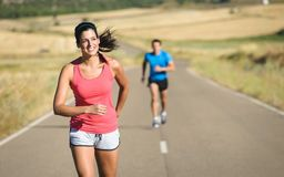 Woman and man running in country road Stock Photos