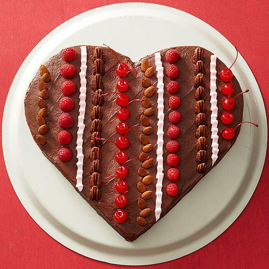 Bake a heart-shape cake for your sweetheart on Valentine's Day. Rows of almonds, raspberries, maraschino cherries, and icing stripe this chocolate-frosted red velvet cake for a sweet and romantic treat.
