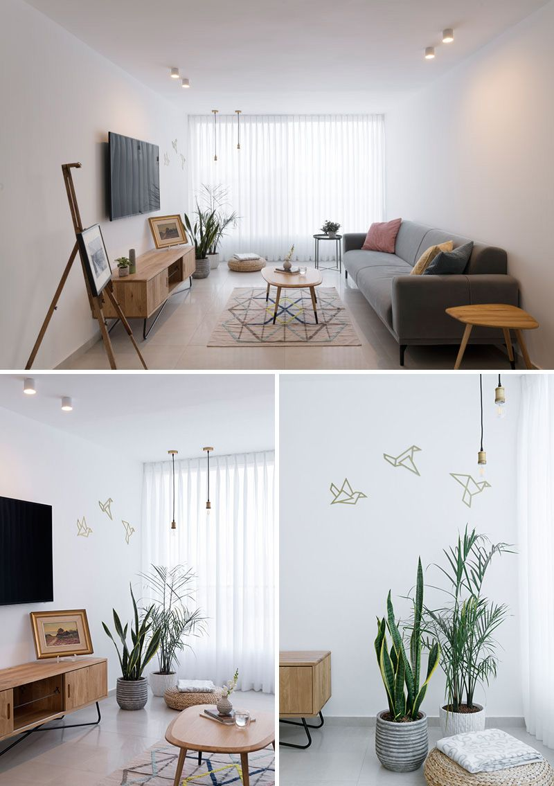 In this modern apartment living room opaque white curtains cover a floor to ceiling window a grey upholstered sofa and light wood furniture give the room