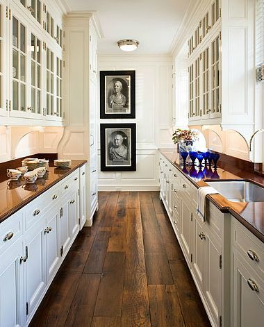 galley kitchen - wood floors, white cabinets, glass cabinets above ...