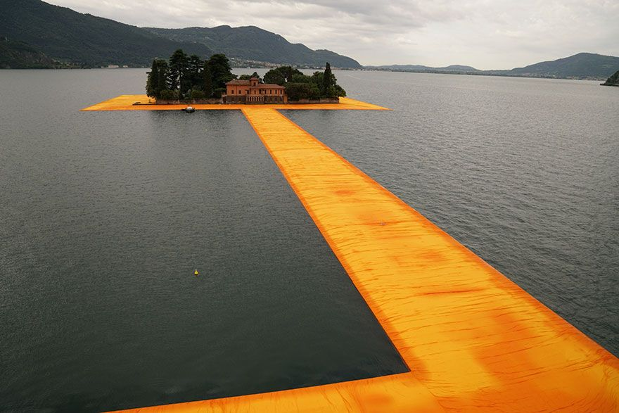 """Jeanne-Claude's, major installation – """"The Floating Piers"""". This 3km (almost 2 miles) floating walkway across Italy's lake Iseo is made of 200,000 high-density polyethylene cubes and is covered in 100,000 square meters of shimmering yellow fabric, which changes colors throughout the day to a shimmering gold and a reddish hue when wet. Here visitors are able to walk from Sulzano to Monte Isola and to the island of San Paolo, which it encircles."""