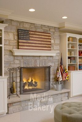 This is a Media Bakery licensable image titled 'FIREPLACES: contemporary country, stone fireplace, suspended mantel, wooden american flag, book shelves on either side, ottoman, flags in a watering can' by artist Jessie Walker for editorial and commercial use only. No use with out payment. Search our large selection of royalty free and rights managed stock photos.