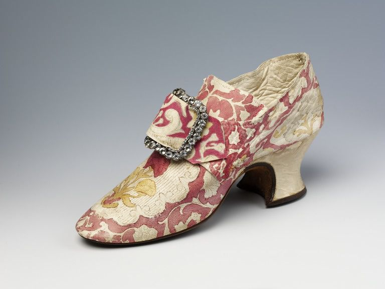 Hoses, Brussels, 1760s (made), kid leather with painted design, and silk satin covered heel. This pair of elegant women's shoes, in kid leather, is beautifully decorated with a painted design. The pattern on the toe, with its flower, vertical lines and scalloped edges, resembles Brussels bobbin lace. The latchets would have been fastened with a buckle. In 1767 Lady Mary Coke recorded in her diary that she had bought six pairs of painted shoes from a shop in Brussels.
