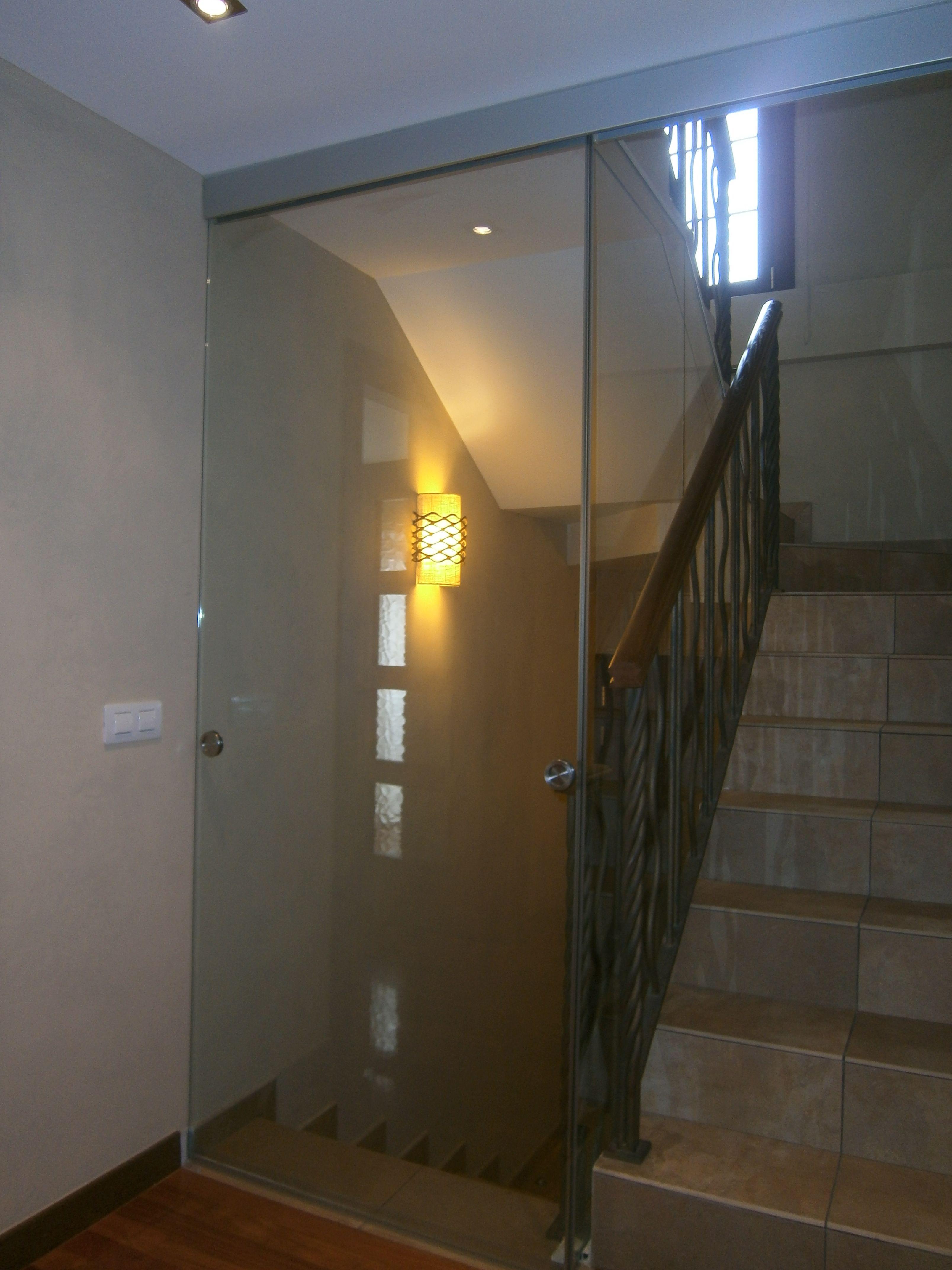 Puerta corredera de cristal para cerrar escalera con una for Colocar puerta corredera