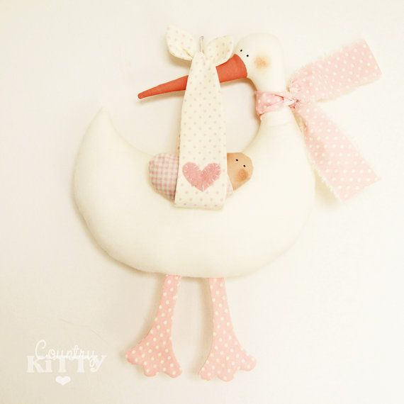 (scendi piú sotto per le descrizione in italiano - scroll down for italian description)  This is a stork softie newborn decoration designed and handmade by me. The stork is made in white cotton, it has a painted beak and its keeping a newborn baby girl in a cloth from her beak. On the belly of the stork I can handstitch the name of the baby (included in the price) or leave it blank as it is at the moment. I will handstitch the name using my own freestyle calligraphy, you have a few examples…
