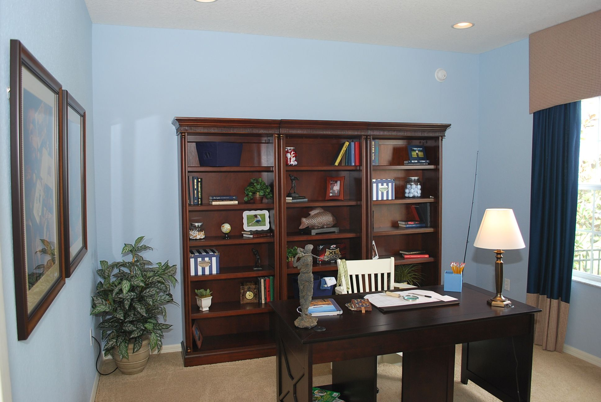 Blue is a calming color - and not just for baby's rooms!  It pairs well with dark wood in this room to create a home office with a soothing vibe.  Highland Homes Williamson II model home.
