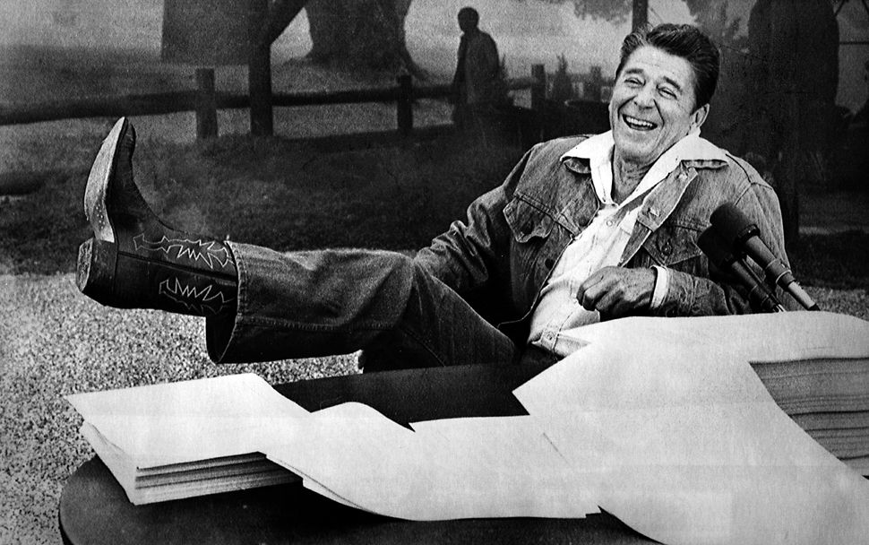 Aug. 13, 1981: During a press conference at his ranch near Santa Barbara, President Reagan shows a boot following questions regarding a bubonic plague threat near his ranch. In front of him lies the economic tax relief bill and budget which he signed.