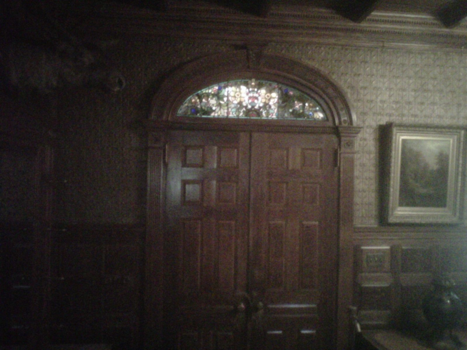 The front doors in the grand entrance notice the arched glass above