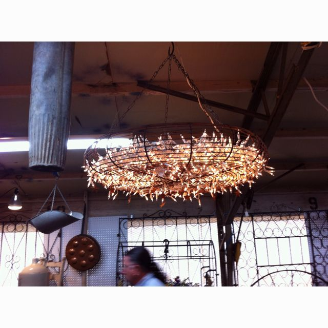 Chandelier made by using a large fan guard, filling it with strings of white Christmas lights & small Texas metal stars hang from the old fan guard. Shabby Chic??
