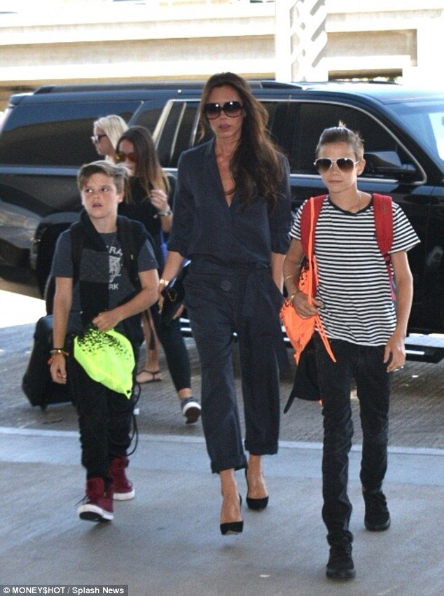 David Beckham cradles Harper as he arrives at LAX airport with family