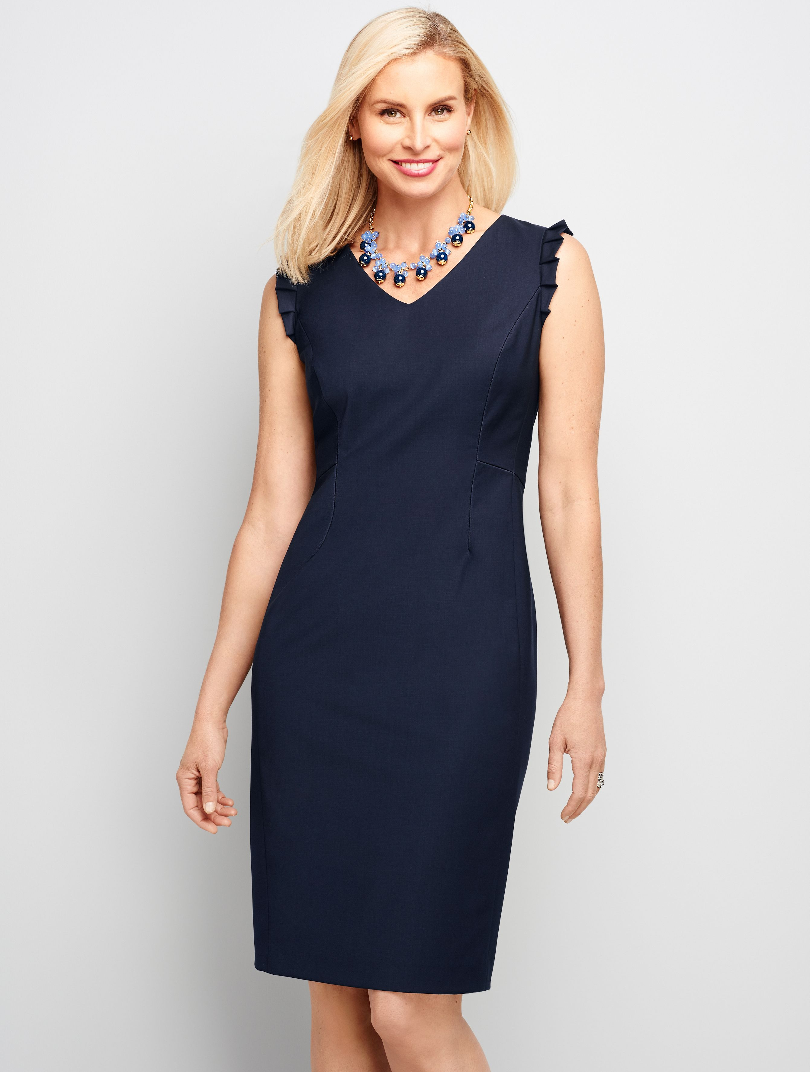 71000552 A classic sleeveless dress with a subtle ruffle detail at the sleeveless  arm opening is the perfect dress on its own or under a cardigan.