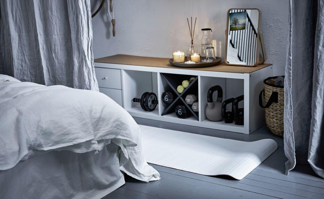 Treningsutstyr er oppbevart på soveromsveggen på knagger og hyller, med ei yogamatte rullet ut på gulvet foran.