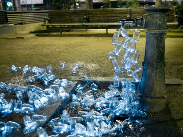 The latest installation of Luzinterruptus uses 200 glass bottles to create a surprisingly poetic comment on Madrid's vanishing public fountains. Mimicking water, they spout out of four fountainheads and run through the street in luminous streams.