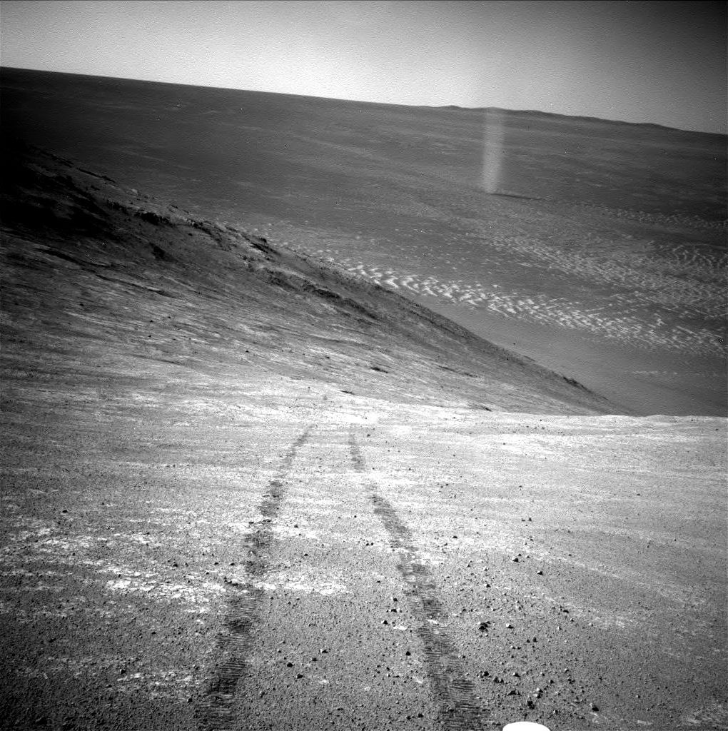 "From its perch high on a ridge, NASA's Mars Exploration Rover Opportunity recorded this image of a Martian dust devil twisting through the valley below. The view looks back at the rover's tracks leading up the north-facing slope of ""Knudsen Ridge,"" which forms part of the southern edge of ""Marathon Valley."" Opportunity took the image using its navigation camera (Navcam) on March 31, 2016, during the 4,332nd Martian day, or sol, of the rover's work on Mars."