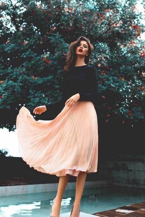 Elegantes Outfit mit rosa Plissee Rock. Klassisch Rock mit schwarzem  Pullover. Dazu Make-up mit dunklen Lippen.