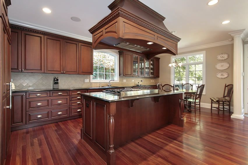 A Luxury Kitchen With Mahogany Cabinets And Cherry Wood Flooring