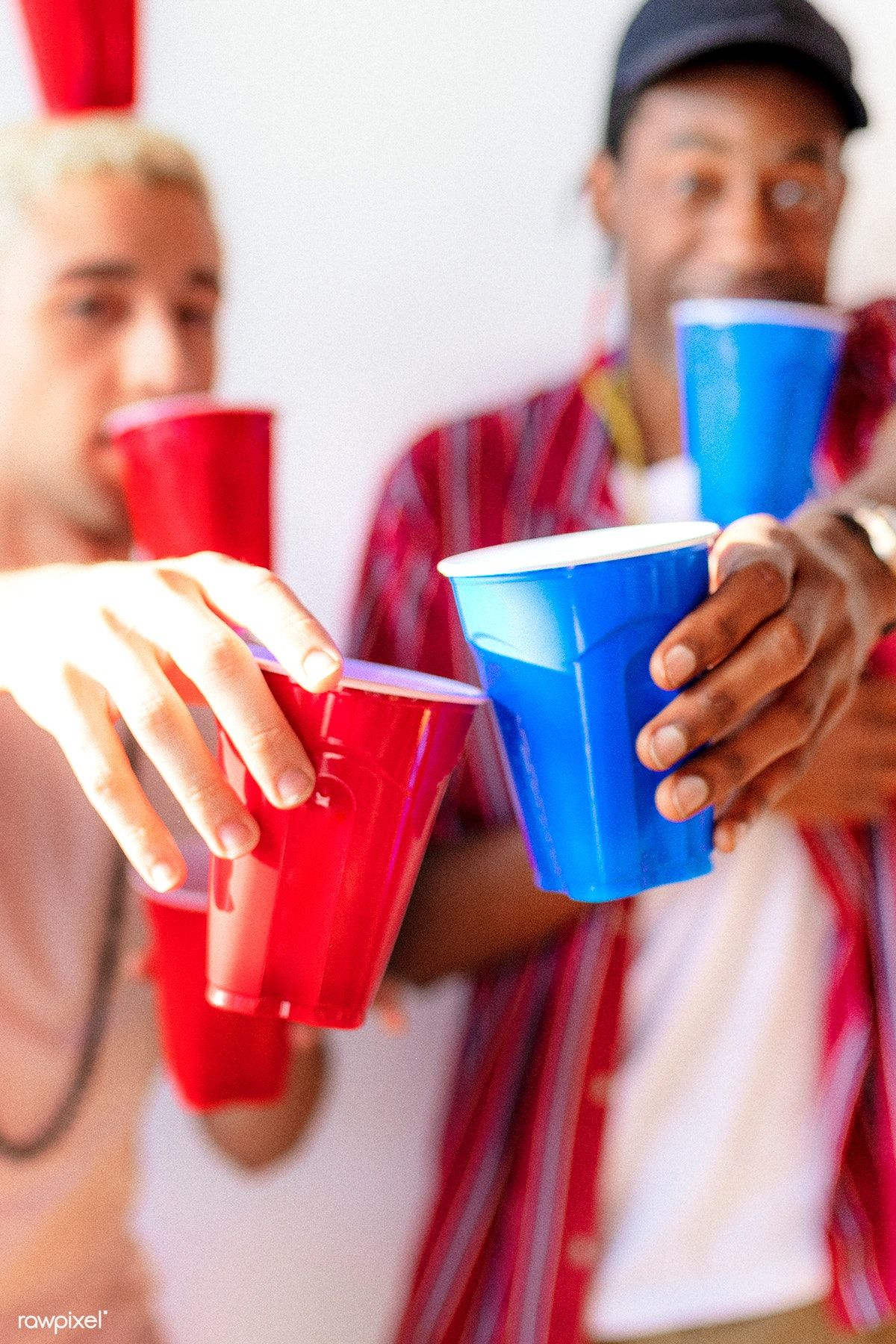 Download premium photo of Cheerful young men holding cups