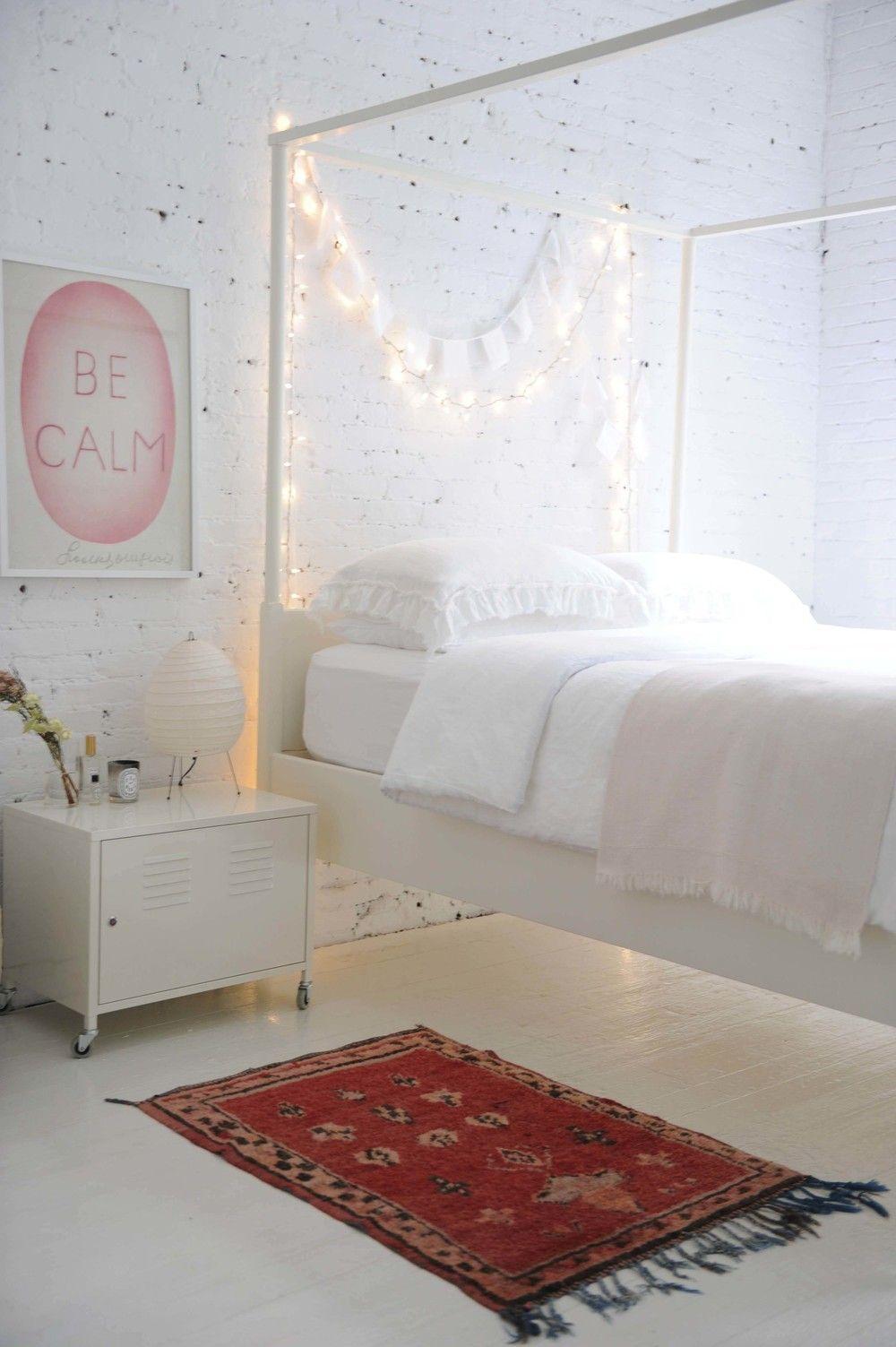 Une chambre avec lit à baldaquin et guirlande lumineuse