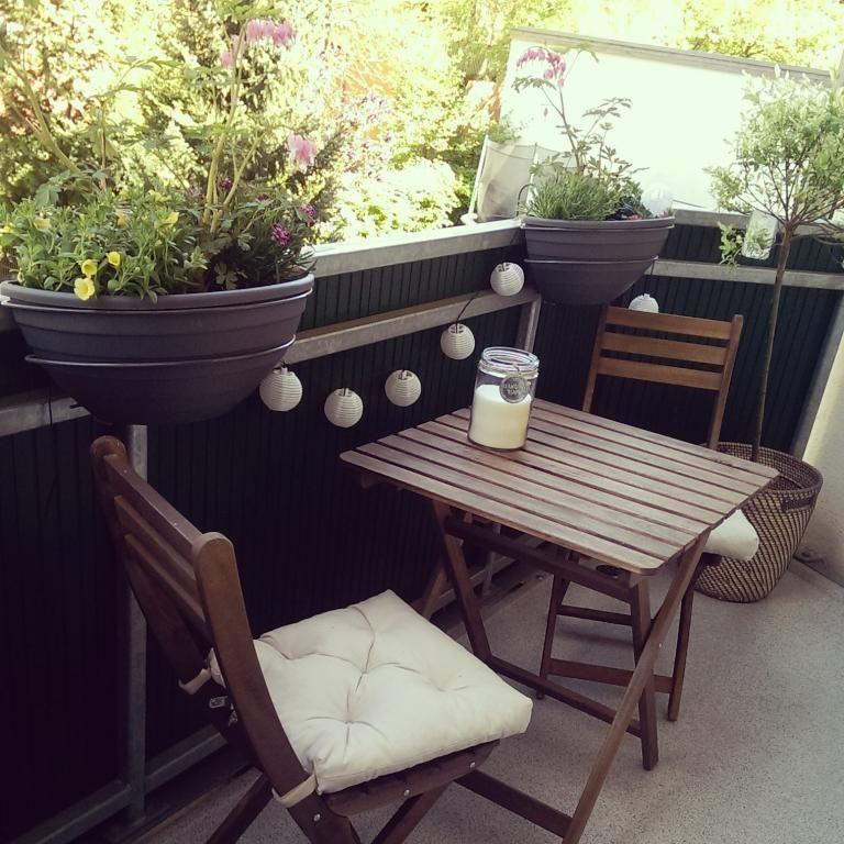 sch ner balkon mit holzm bel und lampions mit blick auf den gr nen innenhof balkon balcony. Black Bedroom Furniture Sets. Home Design Ideas