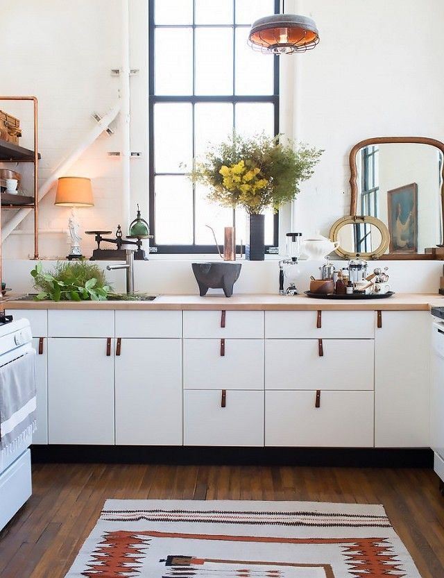 Rustic kitchen with IKEA cabinents, leather pulls, and a retro industrial pendant light