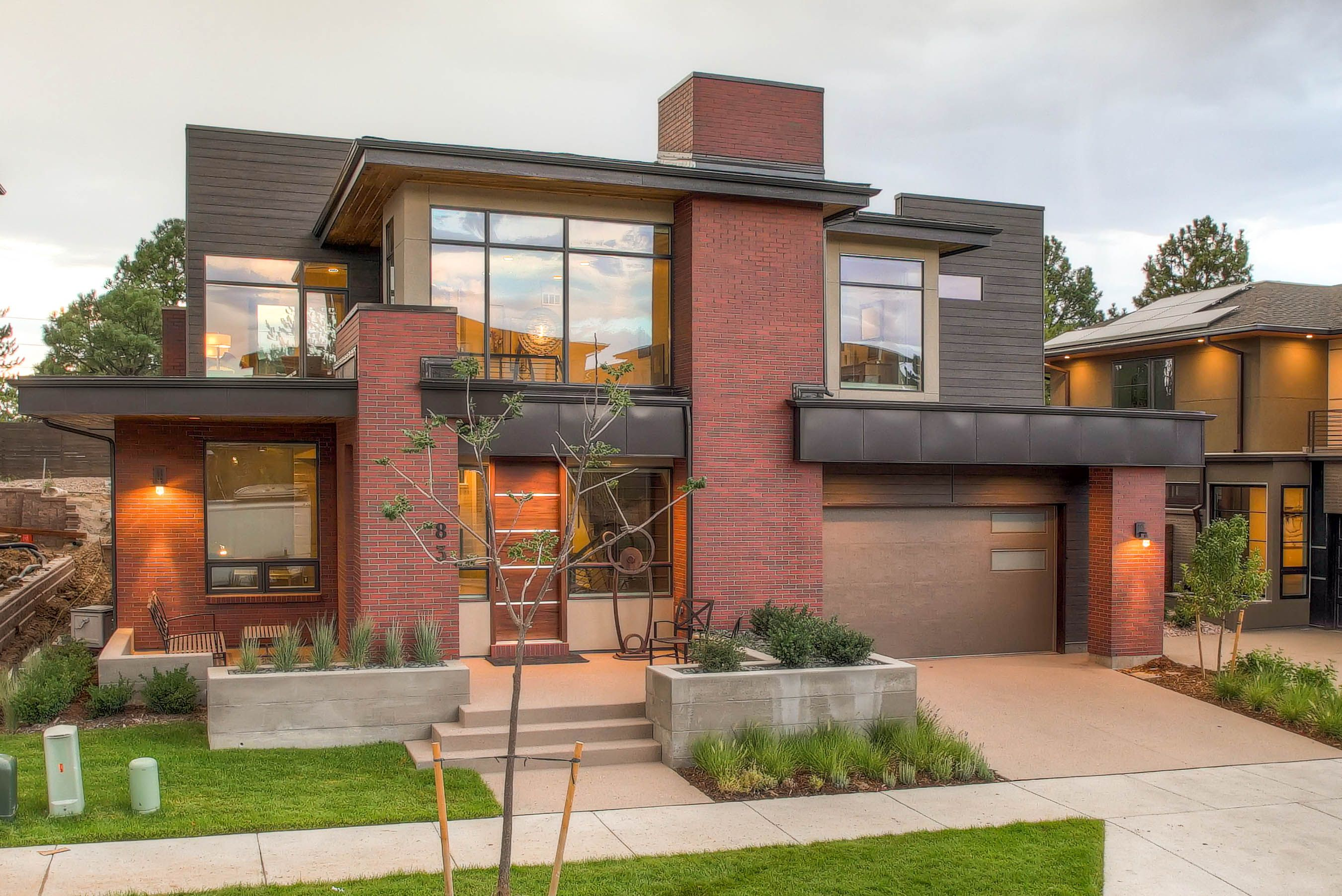 The Very Modern Exterior Of The Home Features Red Brick And Dark