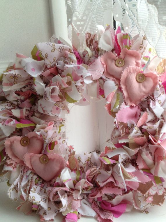Handmade rag wreath using four different fabrics with tones of white pink and green finished with four padded hearts. Perfect to adorn the wall of
