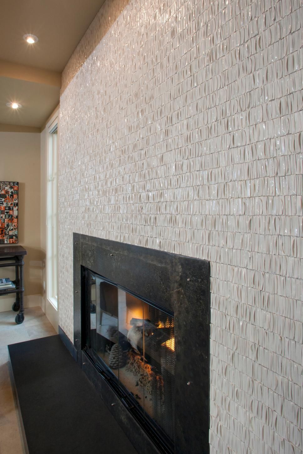 Textured Beige Tiles Surround This Black Fireplace Creating Contrast And Visual Interest Kostyor