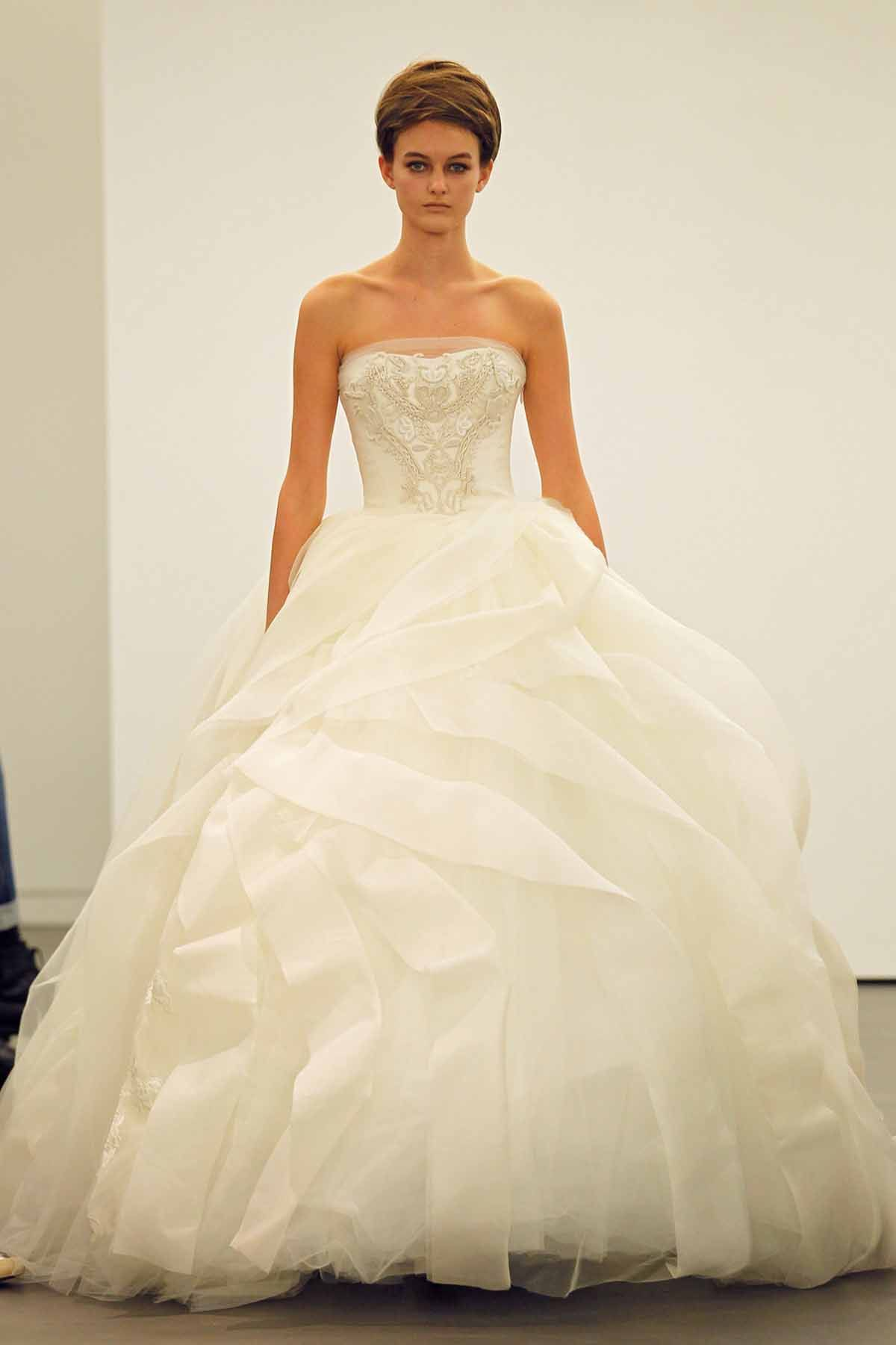 Strapless ball gown with ribbon embroidered bodice and silk organza floating flange skirt accented by lace applique detail at hem.
