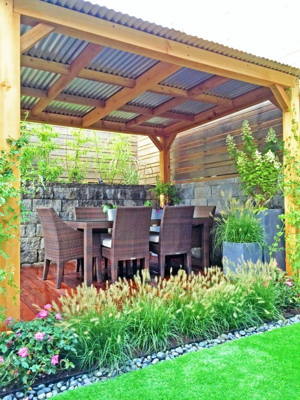 cedar pergola with corrugated tin roof outside the home