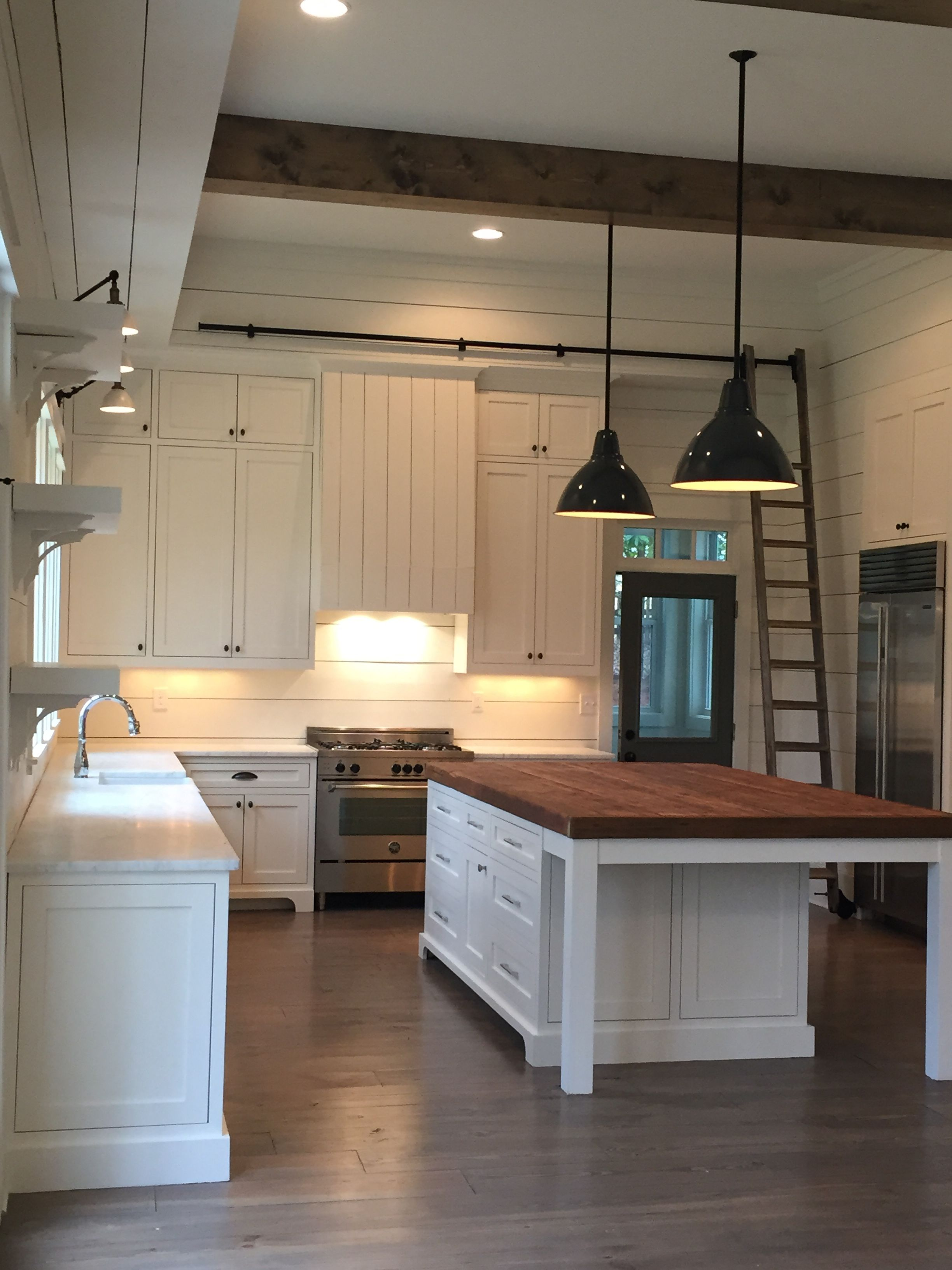 beams pendants, shiplap, island, lights above the sink