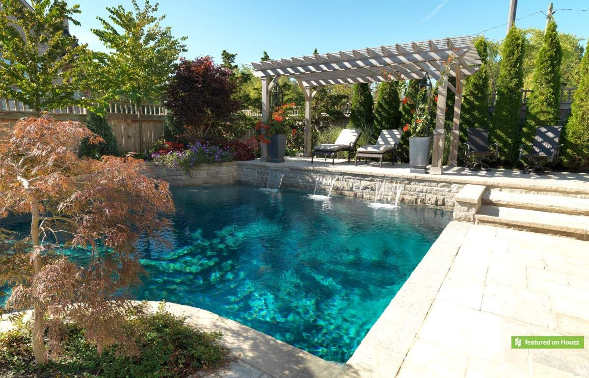 The focal point of this yard is a dry Gunite pool with grey Armourcoat interior. The deck across the deep end has been raised to serve as a diving platform and provide privacy from the nearby street. A pergola structure provides shade for the lounge area while three sheer descent waterfalls add a dramatic touch. The previous and next photo is the same pool. (24 x 33, custom rectangular)